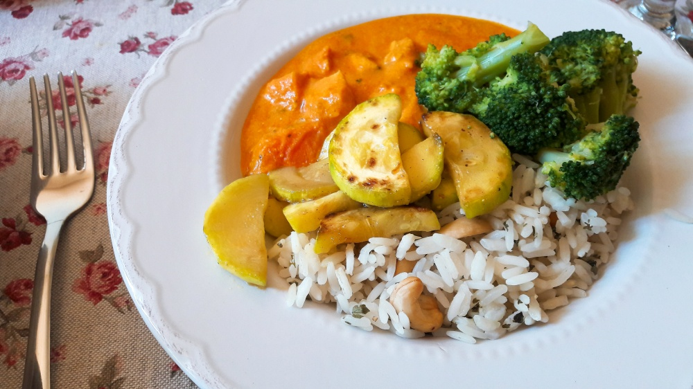 Curry s piletinom i marelicama serviran u bijelom tanjuru.