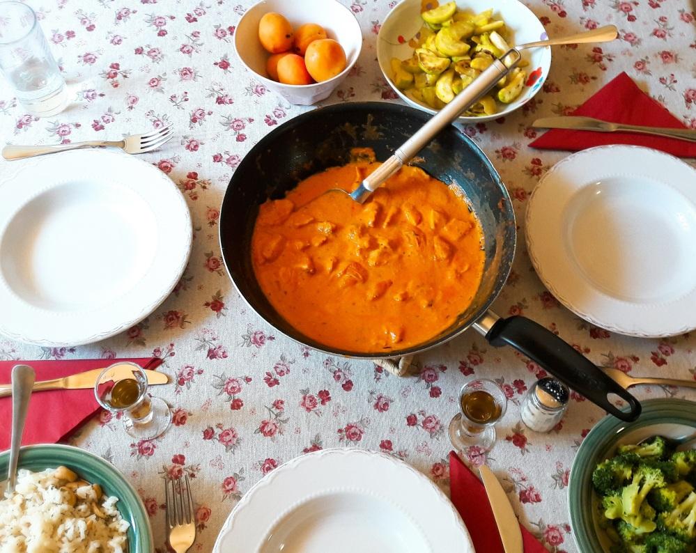 Postavljen stol za ručanje currija s piletinom i marelicama.